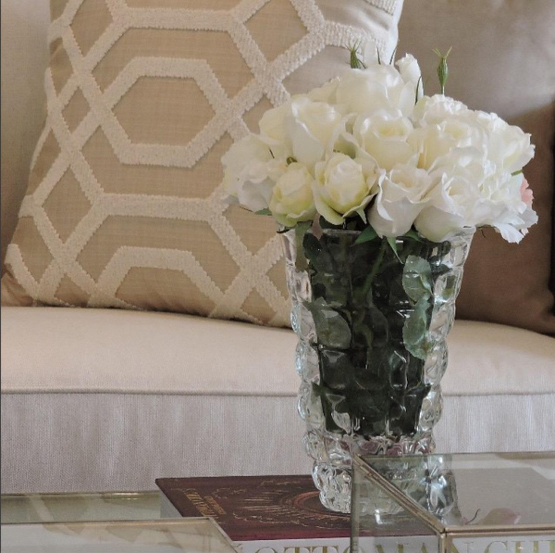 Vaso de cristal com flores na mesa de centro e almofada em tons neutros, da Camélia Decorações - www.cameliadecoracoes.com.be